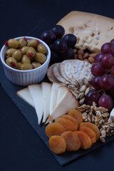 assorted cheese, grapes, crackers, nuts and olive on a black backgtound