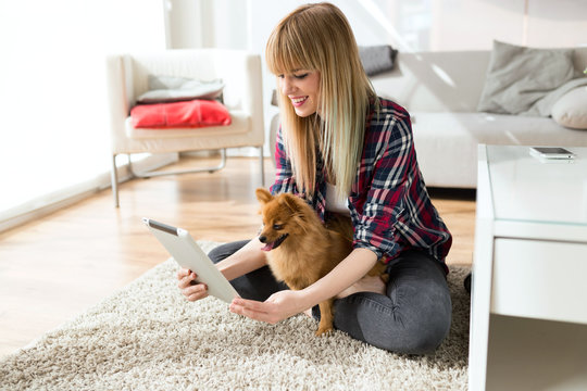 Beautiful young woman with her dog using digital tablet at home.