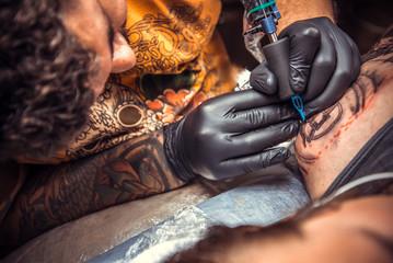 Professional tattooer makes tattoo in tattoo parlor