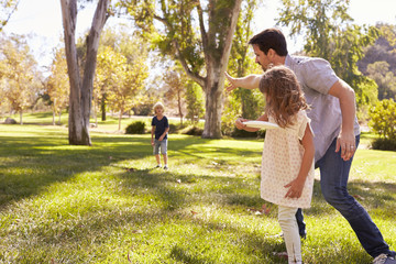 Father With Children Throwing Frisbee In Park Together