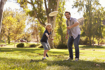 Father Teaching Son To Throw Frisbee In Park