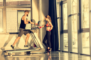 Young sporty woman standing near bearded sportsman training on treadmill