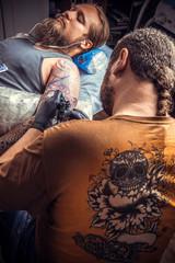 Tattoo master works in tattoo parlor