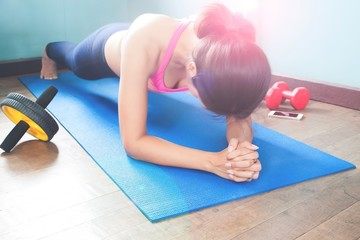 Active woman doing plank on blue yoga mat with fitness equipments, Working out concept