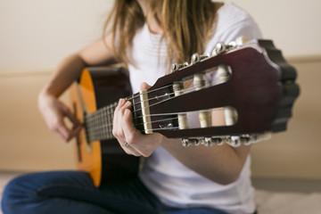 Closeup image of guitar in caucasian woman hands