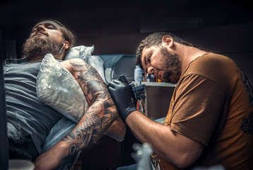 Tattooer makes tattoo pictures in tattoo parlor