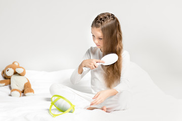 Adorable little girl in pajamas sitting on bed and combing hair
