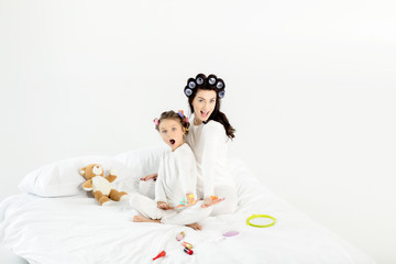 Beautiful mother and daughter in curlers and pajamas having fun on bed