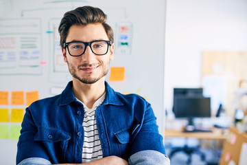 Successful website designer standing with crossed arms