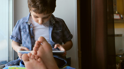PORTRAIT: Cute little boy sits on a windowsill at home and touches a tablet PC