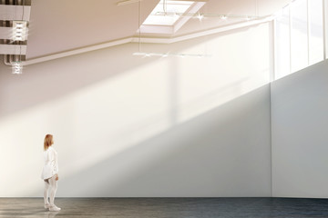 Woman walking near blank white wall mockup in modern gallery