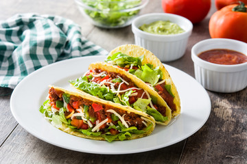 Traditional Mexican tacos with meat and vegetables on wooden background