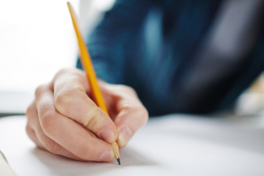 Closeup of male hand holding pencil on blank paper