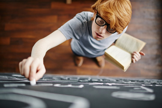 Top view portrait of young red haired man writing on blackboard with chalk holding book in hand while studying in classroom