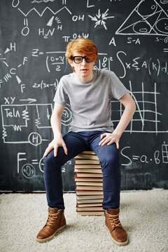 Portrait of modern red haired student sitting on pile of books against blackboard with formulas written in chalk