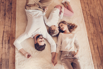 Top view of happy family with one child lying together on carpet