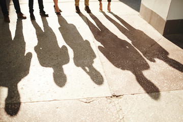 Shadows of five businesspeople standing outdoors, bright sunbeams illuminating shabby asphalt surface Wall mural