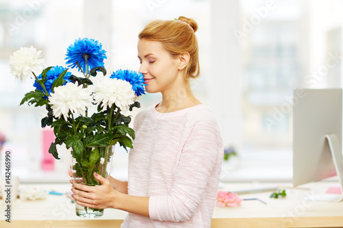 Profile View Of Attractive Young Woman Sniffing Blue