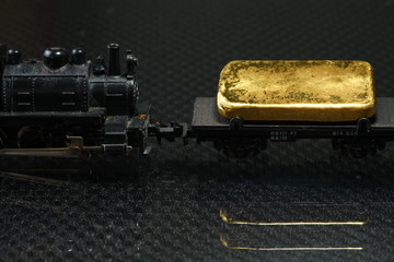 Gold bar put on the on the model railroad flatcar represent the business concept related idea.