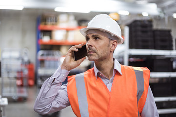 Man in factory hall wearing safety vest and hard hat talking on cell phone