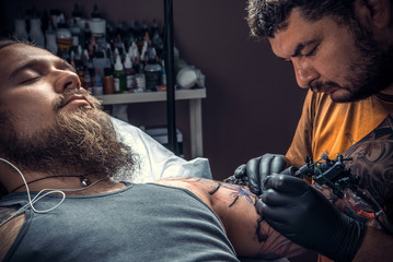 Tattoo master makes tattoo pictures in tattoo studio