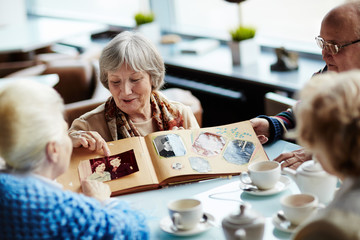 Four senior friends hanging out in lovely coffeehouse: they drinking delicious tea and listening attentively to pretty woman with worn-out photo book in hands
