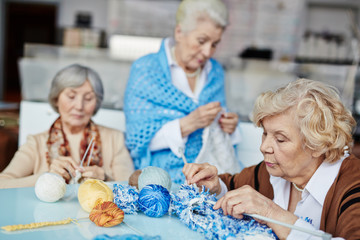 Knitting club for senior people: three concentrated women sitting at table and knitting Christmas presents for their grandchildren