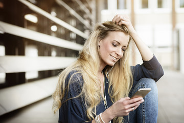 Portrait of smiling blond young woman with earphones looking at cell phone