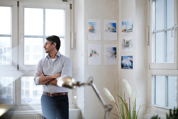 Man in office looking out of window