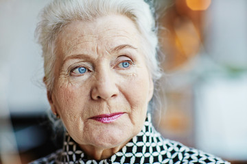 Head shot of beautiful grey-haired senior woman with deep blue eyes looking away thoughtfully, blurred background