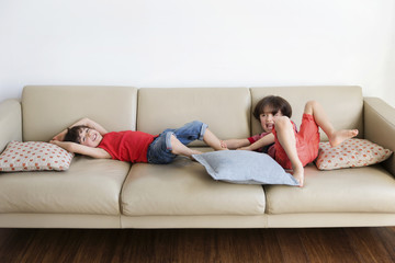 Twin brothers lying on the couch having fun together