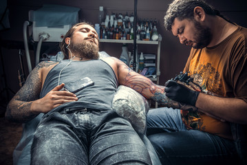 Tattooist making a tattoo in studio