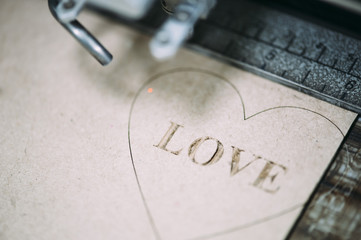 Industrial laser engraving word love on a paperboard