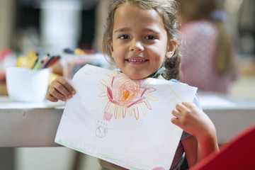 Smiling girl showing drawing