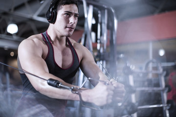 Focused male using cable exercise equipment at gym
