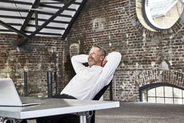 Smiling businessman sitting at table in a loft leaning back
