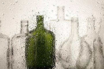 Still life of bottles behind wet glass on a light background.