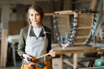 Waist-up portrait of confident fair-haired woodworker with tape measure in hands posing for photography while standing on background of workshop
