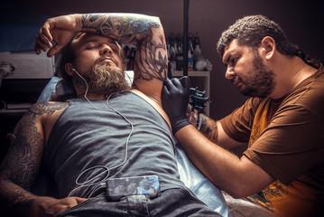 Professional tattooer create tattoo in tattoo studio