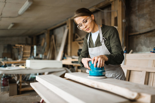 Assiduous young woodworker wearing safety glasses and apron while using electric sander in spacious workshop, waist-up portrait
