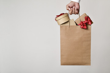 man with a shopping bag full of gift boxes