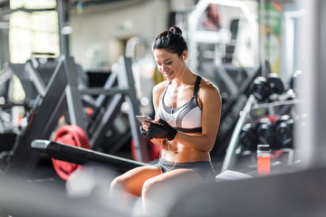 Portrait of smiling slim woman listening to music using smartphone while sitting on bench among machines before work out  in gym