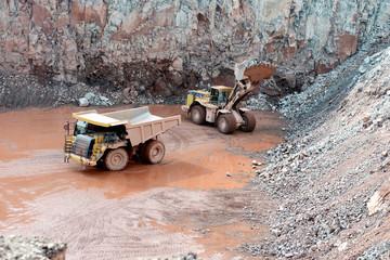 quarry mine of porphyry rock. earthmover loading a dumper truck