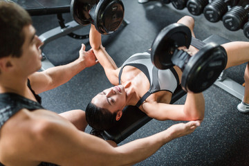 Top view portrait of muscular personal instructor helping beautiful woman doing weightlifting exercise with big dumbbells on bench  in modern gym