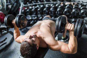 Portrait of shirtless muscular man doing bench press working out with dumbbells during strength training in modern gym