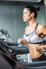 Close view portrait of sportive brunette woman  running on treadmill in gym listening to music using shoulder smartphone holder