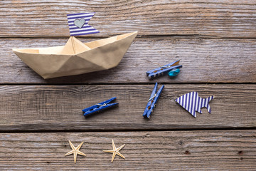 Paper ship and fish on wooden background.