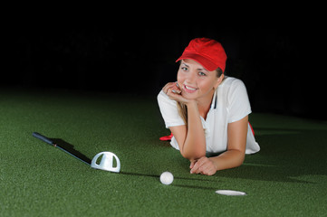 Young female golf player on artificial field at the mini golf club
