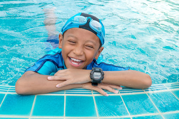 Portrait of a boy smiling in public swimming pool