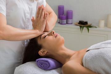 Woman beautician doctor make head massage in spa wellness center